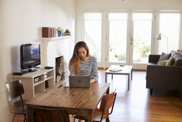 Woman working from home using a laptop on dining table